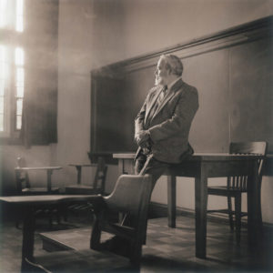 Valdes leans against a desk in an empty classroom